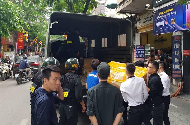 Gần 20 thùng các-tông được cảnh sát đưa từ cửa hàng trên phố Lý Quốc Sư lên chiếc xe tải thứ nhất. Ảnh: Tất Định